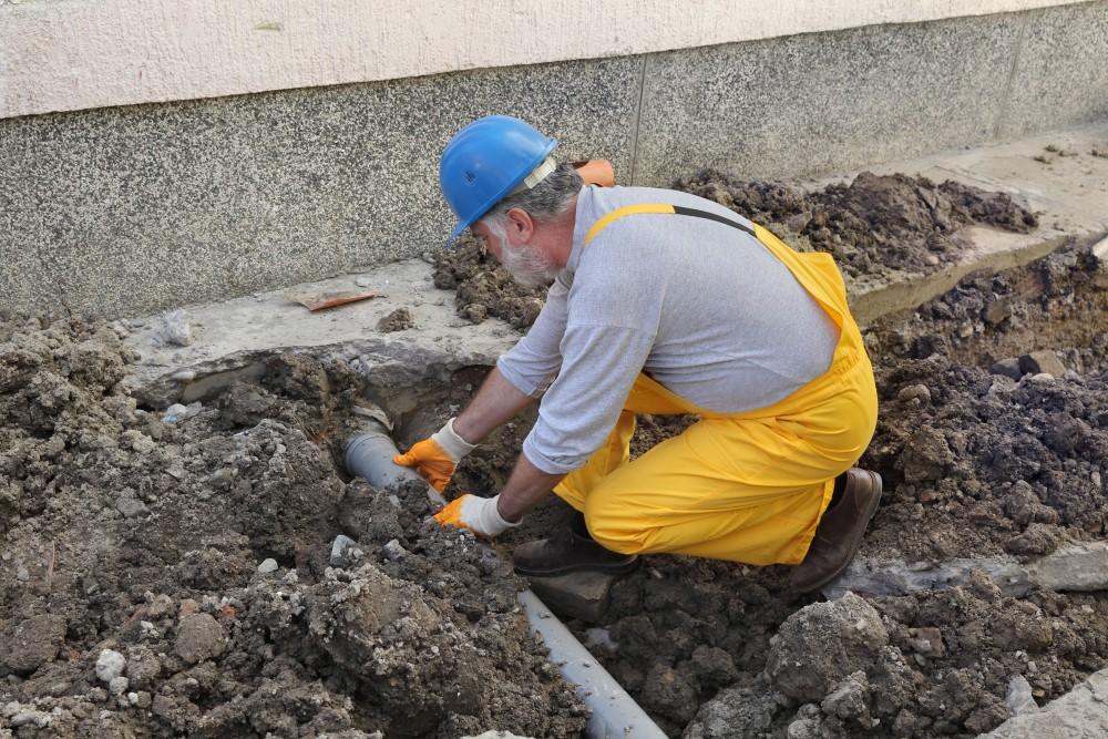 hydraulik podłącza rurę instalacji kanalizacyjnej